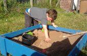 A Sand Box avec couvercle fait des planches traitées clôture.