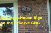 Faisant un signe de la maison en bois sur commande numérique par ordinateur