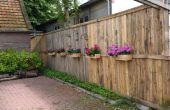 Une clôture de palette avec boîtes à fleurs et les abeilles Hôtels